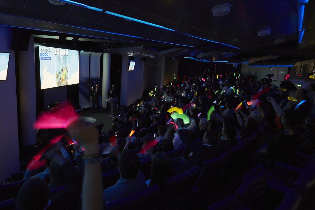 Audience waving their glow sticks in the dark