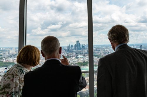 Catherine Grinyer, Gary Moore and Alan Brooks looking out of window at the view of London
